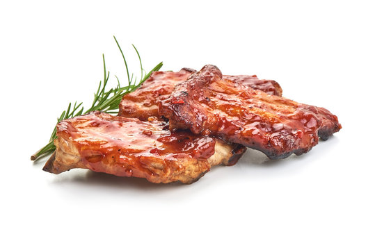 Delicious grilled pork ribs in BBQ sauce with herbs, isolated on white background.
