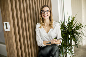 Young businesswoman with digital tablet by the wall in modern office