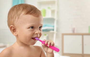 Cute little boy with toothbrush on blurred background