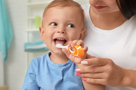 Woman and her son with toothbrush on blurred background