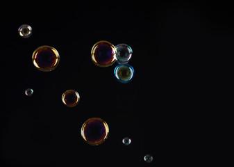 Beautiful translucent soap bubbles on dark background