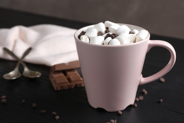 Tasty hot chocolate with milk and marshmallows in cup on table