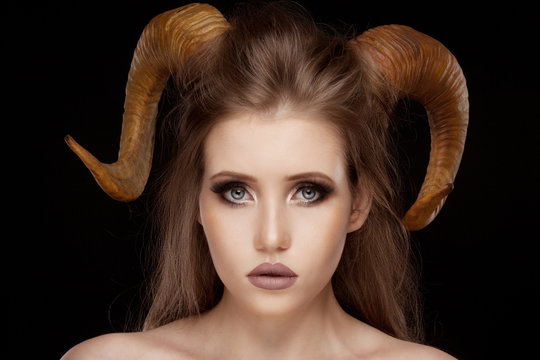 Portrait of an attractive demon woman with horns and curly hair, studio shot for Halloween