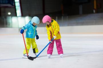 Children play ice hockey. Kids winter sport.