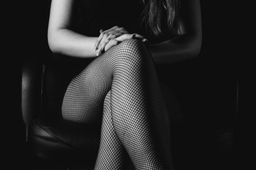 Girl in black fishnet stockings and high heels in the room. Sexy woman in stockings sitting on chair