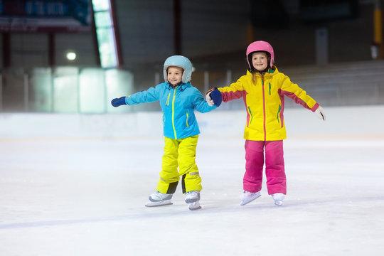 Children skating on ice rink. Kids winter sport.