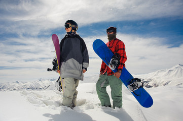 Girl and boy standing in the mountains with snowboards