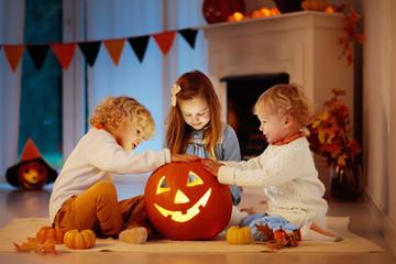 Kids carving pumpkin on Halloween. Trick or treat.