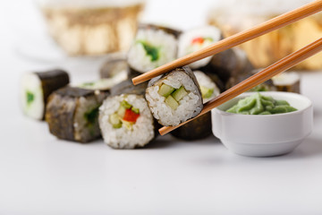 Chopsticks holding roll Philadelphia with marinated rice, cheese Philadelphia