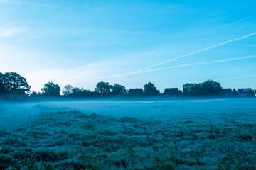 Nebelschwaden am frühen Morgen mit Dorf im Hintergrund. - Standort: Deutschland, Nordrhein - Westfalen, Borken