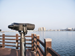 Observation binoculars on the pier and Sokcho city on the background, South Korea