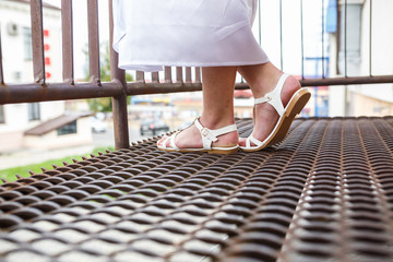 female feet in sandals and robe on iron balcony
