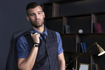 Brutal handsome man holding a jacket on his shoulder against the background of an apartment interior. A stylish guy in a suit. Luxurious rich young man with a fashionable hairstyle.