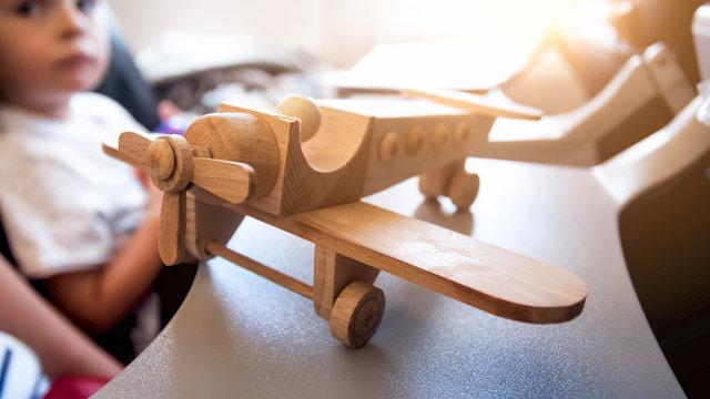 Closeup image of wooden toy plane in airplane against sun shining through illuminator