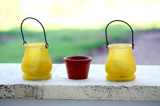 Small yellow and terracotta pots, on a stone ledge, with bright out of focus background