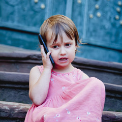 Little beautiful child girl using smart phone as symbol of work or study. Connect to the Internet with smartphone.