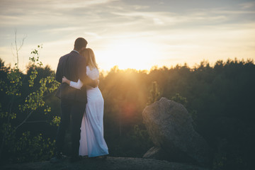 loving wedding couple looking to the sunset