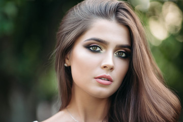 Portrait of a beautiful brunette girl with green eyes. In a city park on a green background. Close-up.