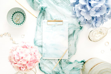 Artist home office desk workspace with watercolor clipboard, paintbrush, turquoise blanket, colorful pastel hydrangea flower bouquet, woman fashion accessories on white background. Flat lay.
