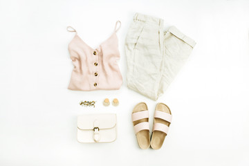 Flat lay, top view travel fashion look with woman clothes and accessories on white background. Female minimalist boho style concept.