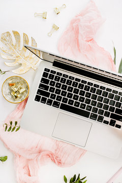 Female home office desk with laptop, pink hydrangea flowers bouquet, pastel blanket, monstera leaf plate and accessories on white background. Flat lay, top view rose gold workspace.
