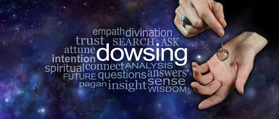 Dowsing with crystal pendulum word cloud - female hand holding a clear quartz crystal dowsing pendulum over hand on a wide cosmic dark night sky background with a DOWSING word cloud on left side