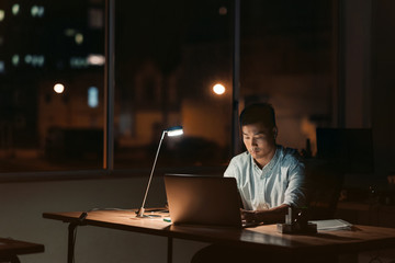 Asian businessman working alone in a dark office at night