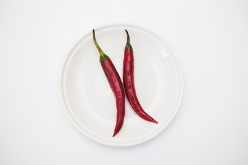Top view of Red hot Peppers on white plate over white background