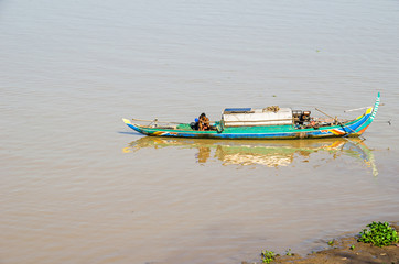 Long-tail wooden boat with a Cambodian family living on it on the Mekong River