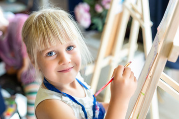 Cute blond smiling girl painting on easel in workshop lesson at art studio. Kid holding brush in hand and having fun drawing with paints. Child development concept