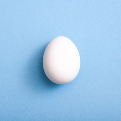 A white egg on blue background