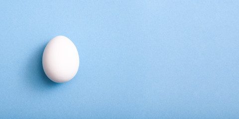 White egg on blue background with copy space