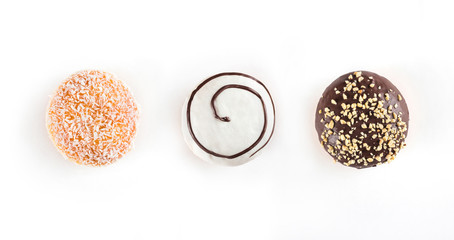 Three sweet doughnuts with chocolate, nuts and coconuts isolated on white background. Top view, flat lay