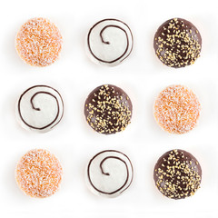 Top view of nine doughnuts different kinds isolated on white background