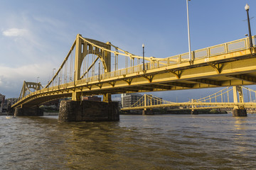 Downtown river waterfront and yellow bridges crossing the Allegheny River in Pittsburgh, Pennsylvania.