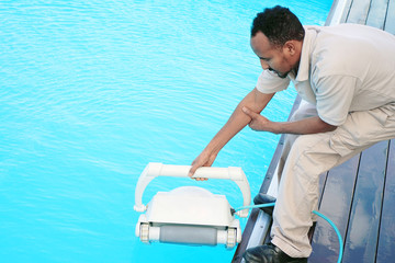 Pool cleaner during his work. Hotel staff worker cleaning the pool.