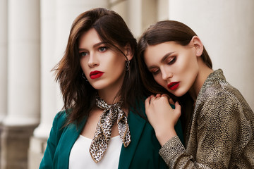 Outdoor close up fashion portrait of two young beautiful women with red lips, wearing trendy clothes and accessories with animal prints,  posing in street of european city. Copy, empty space for text