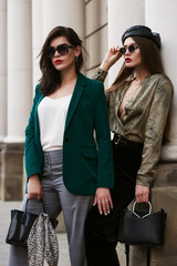 Outdoor fashion portrait of two young beautiful women wearing stylish sunglasses, trendy clothes and accessories with animal prints, holding black leather bags, posing in street of european city