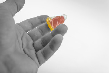 Close-up of a condom in his hand. Contraceptive protection against pregnancy, AIDS.