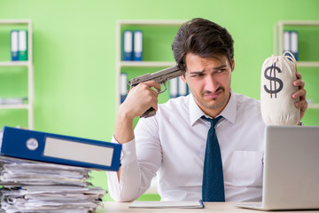 Despaired businessman thinking of suicide in the office