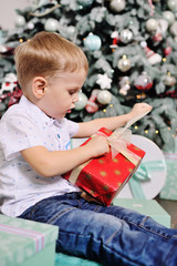 baby boy opens boxes with gifts under the Christmas tree and smiles