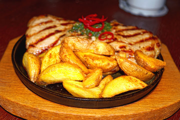 Big pork steak with fried potatoes in a cast iron pan