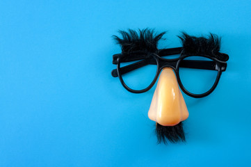 Happy april fool's day and funny pranks concept with a pair of comical glasses with bushy eyebrows and thick mustache isolated on blue background with copy space