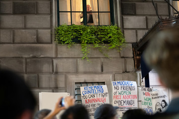A man takes a picture of protesters in front of Yale Club during a protest and march against the U.S. Supreme Court nominee Brett Kavanaugh in New York City