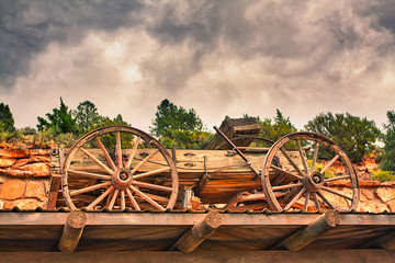 Wooden Cart sitting on top of a roof under a colorful and overcast sky