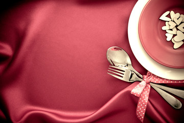 red heart shape with White empty plate with fork and spoon on red silk fabric for love dinner concept
