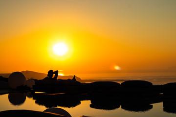 Silhouetted Man watching sunset, Santorini Greece