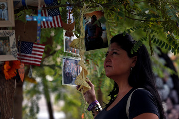 Sabrina Mercadante looks at photos on a tree dedicated to shooting victim Brian Fraser at the Las Vegas Healing Garden during the one-year anniversary of the October 1 mass shooting in Las Vegas