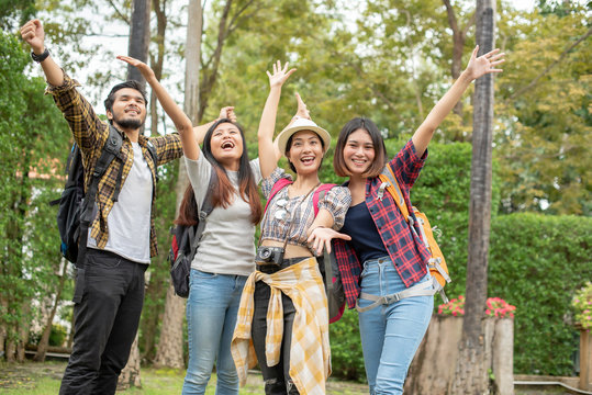 Group Asian people with backpack summer outdoor and happy are taking photo at forest in the evening; Attractive young trusted spend time together; Relax time on holiday concept travel