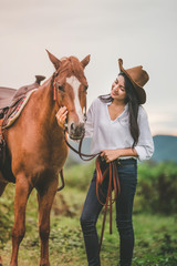 Asian young woman  take care of her blows horse at sunset.